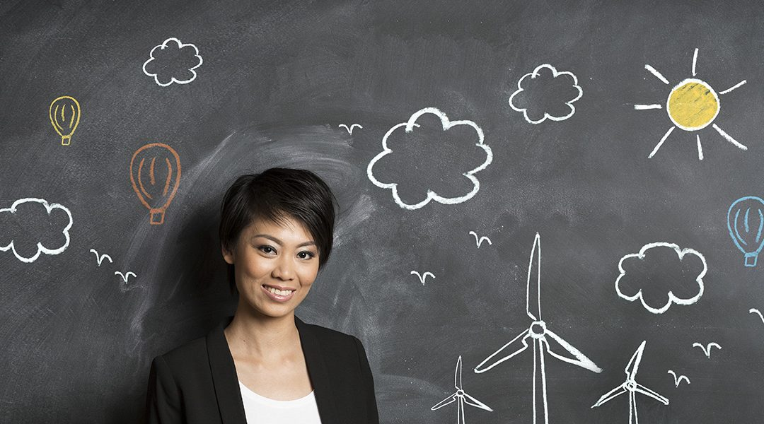 Stock photo woman standing in front of drawn picture of wind turbines